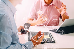 Businessmen working together on a document and using smart phone. And digital tablet and laptop computer in modern office with VR icon diagram Royalty Free Stock Images