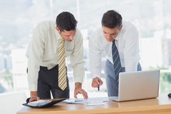 Businessmen working together leaning on desk Royalty Free Stock Images