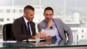 Businessmen working together on a tablet. Businessmen discussing and working together on a tablet stock video footage