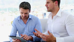 Businessmen working together on tablet pc. In the office stock footage
