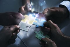Businessmen working together to build a puzzle. Concept of teamwork, partnership, integration and startup. Businessmen working together to build a colored stock image