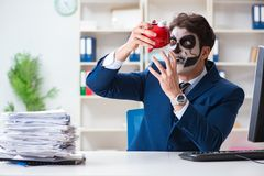 Businessmsn with scary face mask working in office. Businessman with scary face mask working in office Stock Photo