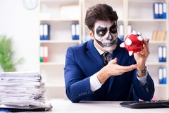 Businessmsn with scary face mask working in office. Businessman with scary face mask working in office Royalty Free Stock Image