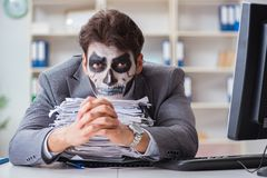 Businessmsn with scary face mask working in office. Businessman with scary face mask working in office Royalty Free Stock Photos