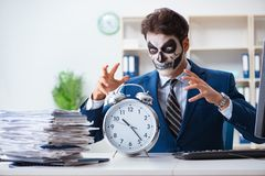 Businessmsn with scary face mask working in office. Businessman with scary face mask working in office Royalty Free Stock Photo