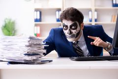 Businessmsn with scary face mask working in office. Businessman with scary face mask working in office Stock Images