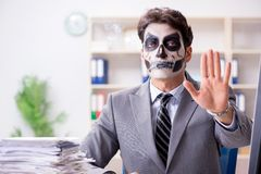 Businessmsn with scary face mask working in office. Businessman with scary face mask working in office Stock Photography