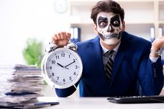 Businessmsn with scary face mask working in office. Businessman with scary face mask working in office Stock Image