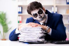 Businessmsn with scary face mask working in office. Businessman with scary face mask working in office Stock Photos