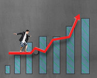Businessnan surfing on growth red arrow with histogram drawing Royalty Free Stock Images