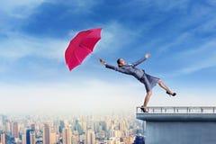 Businessoman die zich op Th-rand met paraplu bevinden royalty-vrije stock afbeeldingen