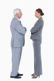 Businesspartner se tenant face à face avec des bras pliés Photographie stock libre de droits