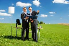 Businesspartners är arbete i en grön äng Royaltyfri Fotografi