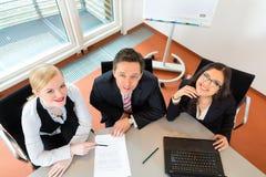 Businesspeople är sammanträde på kontorsskrivbordet arkivbild