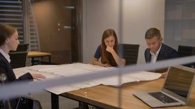 Businesspeople που λειτουργεί με το σχέδιο στο γραφείο απόθεμα βίντεο