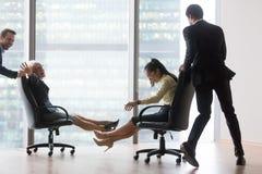 Businesspeople που έχει τη διασκέδαση που οδηγά στις καρέκλες και που γελά σε offic στοκ εικόνα