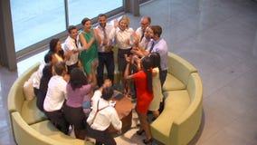 Businesspeople που δίνει σε μεταξύ τους υψηλά πέντε στο λόμπι γραφείων φιλμ μικρού μήκους