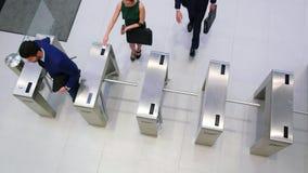 Businesspeople που ανιχνεύει τις κάρτες τους στην πύλη περιστροφικών πυλών απόθεμα βίντεο