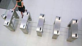 Businesspeople που ανιχνεύει τις κάρτες τους στην πύλη περιστροφικών πυλών φιλμ μικρού μήκους