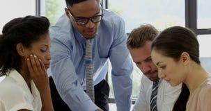 Businesspeople που λειτουργεί μαζί γύρω από έναν πίνακα
