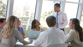 Businesspeople που κάθεται γύρω από τον πίνακα που διοργανώνει τη συνεδρίαση φιλμ μικρού μήκους