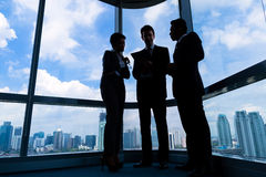 Businesspeople που στέκεται στην εργασία windo γραφείων στοκ εικόνες