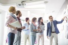 Businesspeople που συζητά πέρα από τα έγγραφα σχετικά με τον τοίχο στο δημιουργικό γραφείο Στοκ Εικόνες