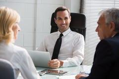 Businesspeople τρία που διοργανώνει μια συνεδρίαση στο γραφείο Στοκ εικόνα με δικαίωμα ελεύθερης χρήσης