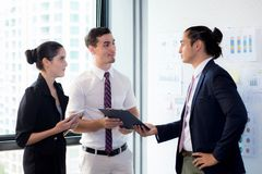 Businesspeople τρία που στέκεται στο σύγχρονο γραφείο που φαίνεται έγγραφο αρχείων και που μιλά στην αίθουσα συνεδριάσεων Στοκ φωτογραφίες με δικαίωμα ελεύθερης χρήσης
