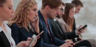 Businesspeople χρησιμοποιώντας την τεχνολογία στην πολυάσχολη περιοχή λόμπι του γραφείου Στοκ Εικόνες