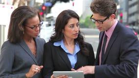 Businesspeople χρησιμοποιώντας την ψηφιακή ταμπλέτα έξω απόθεμα βίντεο