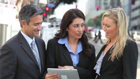 Businesspeople χρησιμοποιώντας την ψηφιακή ταμπλέτα έξω φιλμ μικρού μήκους