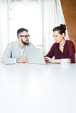 Businesspeople δύο που λειτουργεί και που χρησιμοποιεί το lap-top στη συνάντηση στην αρχή Στοκ εικόνες με δικαίωμα ελεύθερης χρήσης