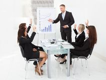 Businesspeople answering businessman in meeting Stock Images