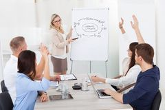 Businesspeople answering businesswoman in meeting Stock Photography
