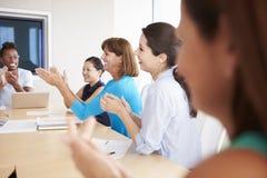 Businesspeople Applauding Colleague In Boardroom Stock Photos