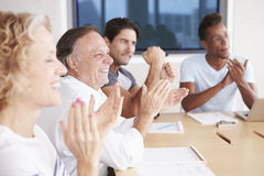 Businesspeople Applauding Colleague In Boardroom Stock Images