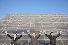 Businesspeople with Arms Outstretched in front of Solar Panel Royalty Free Stock Photos