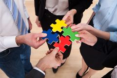 Businesspeople assembling jigsaw puzzle. Close-up Of Businesspeople Holding Multi Colored Jigsaw Puzzle stock photo