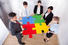 Businesspeople assembling jigsaw puzzle. High Angle View Of Businesspeople Holding Multi Colored Jigsaw Puzzle royalty free stock photos