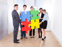 Businesspeople Assembling Jigsaw Puzzle. High Angle View Of Businesspeople Holding Multi Colored Jigsaw Puzzle royalty free stock photo