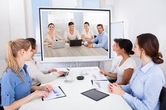 Businesspeople attending video conference. Businesspeople Sitting In Conference Room Looking At Projector Screen Stock Photo