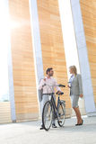 Businesspeople with bicycle conversing outside building Stock Images