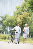 Businesspeople with bicycle conversing while walking on street Royalty Free Stock Image