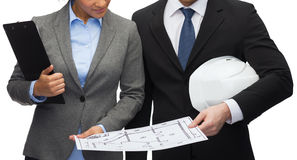 Businesspeople with blueprint and helmet Stock Photography