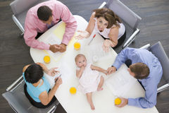 Businesspeople in boardroom with a baby on table Stock Photos