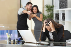 Businesspeople bullying a colleague at office. Two businesspeople bullying a sad colleague that is sitting in her workplace at office stock photo