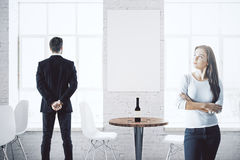 Businesspeople in cafe with poster. Young thoughtful businessman and women in bright white cafe interior with city view, wine on table and empty poster. Mock up Stock Photography