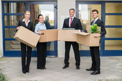 Businesspeople With Cardboard Box Moving Into New Office. Happy Group Of Businesspeople With Cardboard Box Moving Into New Office Stock Photography