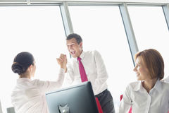 Businesspeople celebrating success in office Royalty Free Stock Images